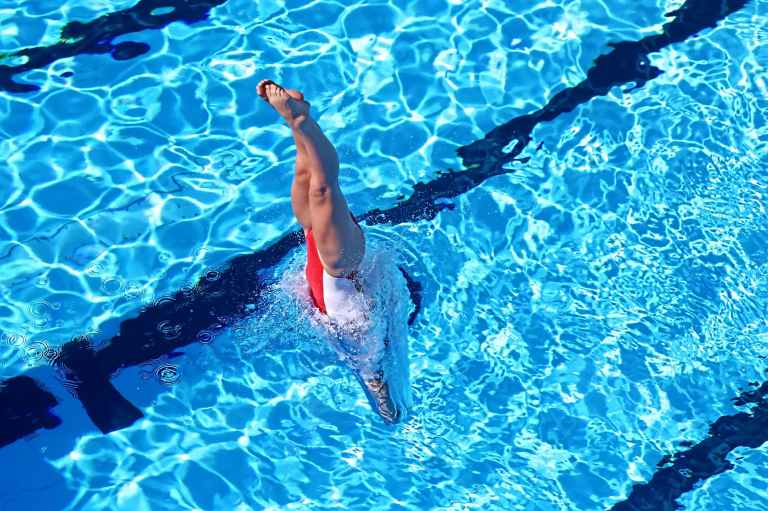 woman in white and red swimsuit idiving in water