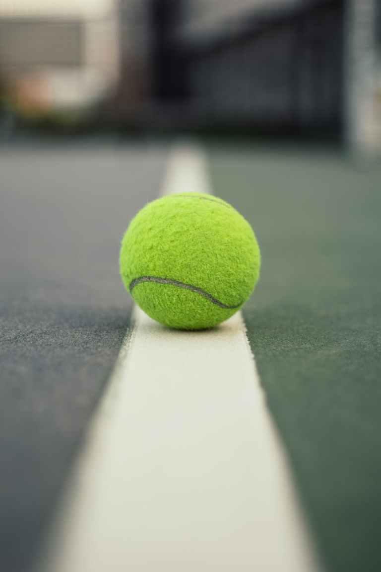 green tennis ball on court