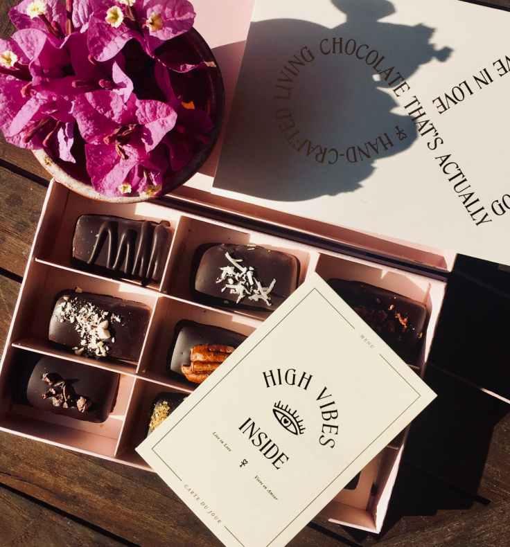 box of chocolates beside bougainvillea flower arrangement
